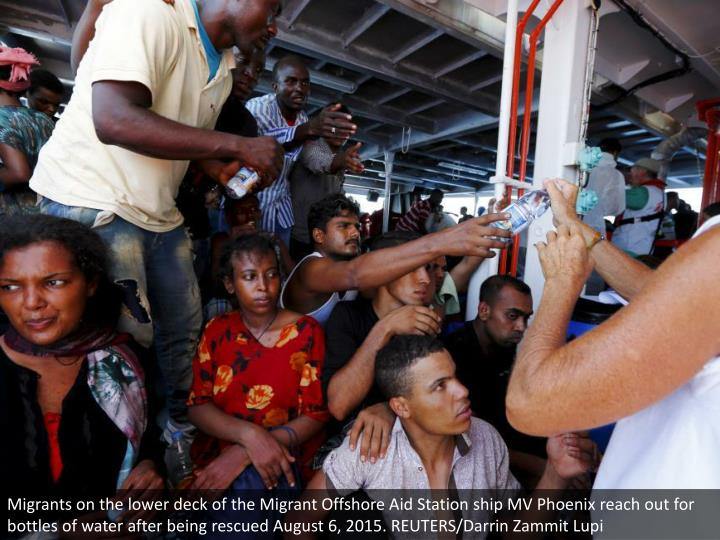 Migrants on the lower deck of the Migrant Offshore Aid Station ship MV Phoenix reach out for bottles of water after being rescued August 6, 2015. REUTERS/Darrin Zammit Lupi