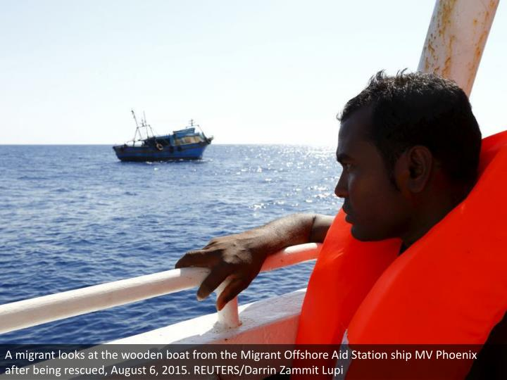 A migrant looks at the wooden boat from the Migrant Offshore Aid Station ship MV Phoenix after being rescued, August 6, 2015. REUTERS/Darrin Zammit Lupi