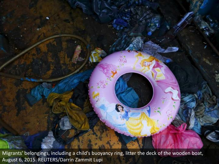 Migrants' belongings, including a child's buoyancy ring, litter the deck of the wooden boat, August ...