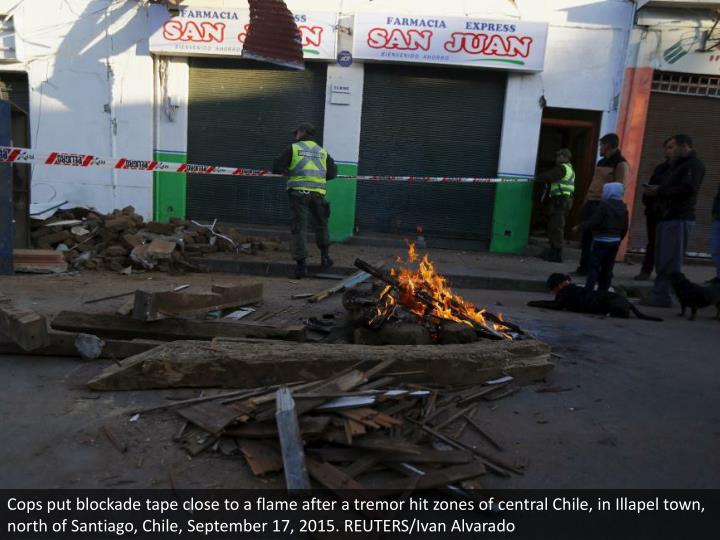 Cops put blockade tape close to a flame after a tremor hit zones of central Chile, in Illapel town, north of Santiago, Chile, September 17, 2015. REUTERS/Ivan Alvarado