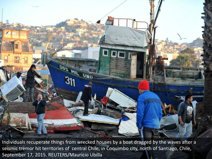 Individuals recuperate things from wrecked houses by a boat dragged by the waves after a seismic tre...