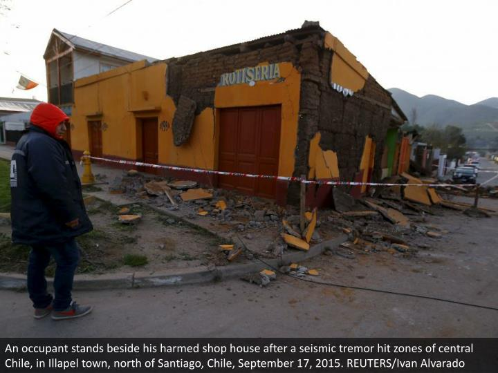 An occupant stands beside his harmed shop house after a seismic tremor hit zones of central Chile, in Illapel town, north of Santiago, Chile, September 17, 2015. REUTERS/Ivan Alvarado