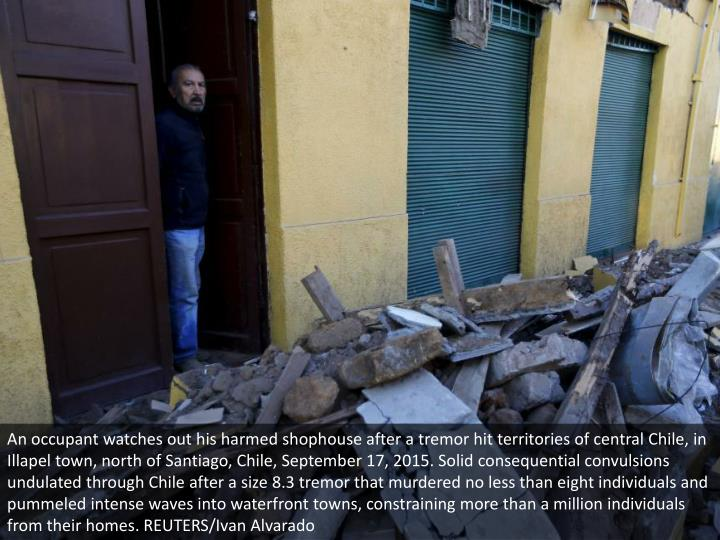 An occupant watches out his harmed shophouse after a tremor hit territories of central Chile, in Ill...