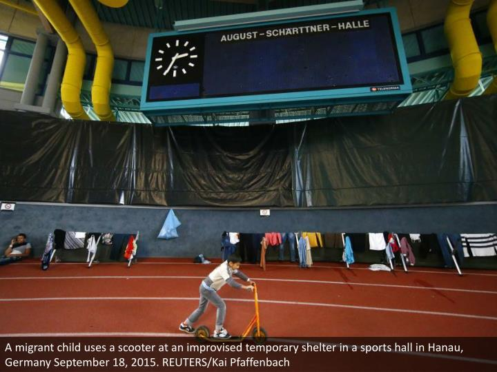 A migrant child uses a scooter at an improvised temporary shelter in a sports hall in Hanau, Germany September 18, 2015. REUTERS/Kai Pfaffenbach