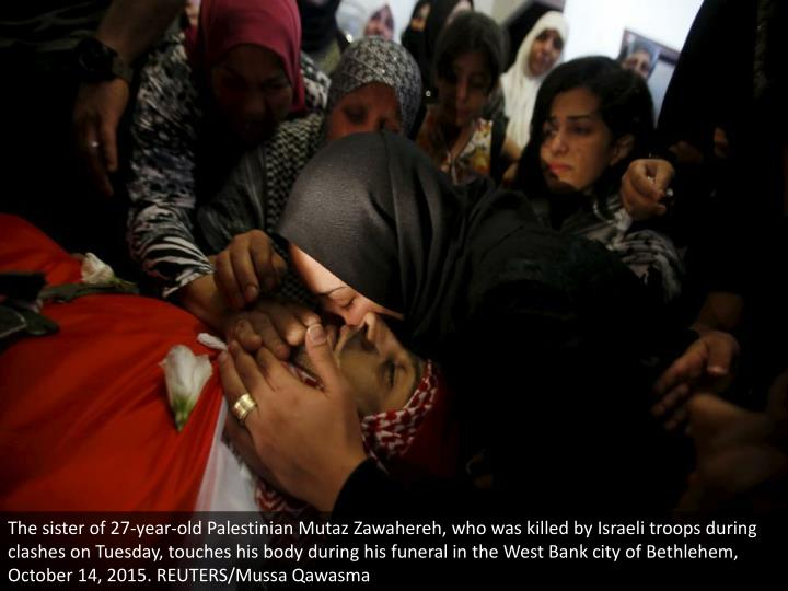 The sister of 27-year-old Palestinian Mutaz Zawahereh, who was killed by Israeli troops during clashes on Tuesday, touches his body during his funeral in the West Bank city of Bethlehem, October 14, 2015. REUTERS/Mussa Qawasma