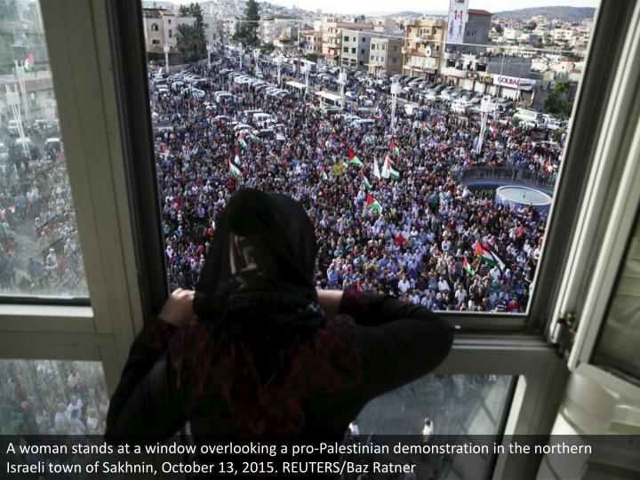 A woman stands at a window overlooking a pro-Palestinian demonstration in the northern Israeli town of Sakhnin, October 13, 2015. REUTERS/Baz Ratner