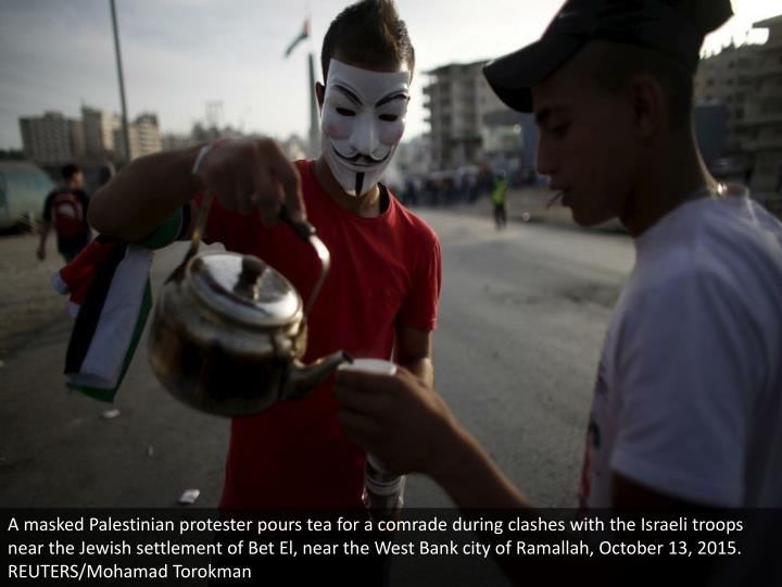 A masked Palestinian protester pours tea for a comrade during clashes with the Israeli troops near the Jewish settlement of Bet El, near the West Bank city of Ramallah, October 13, 2015. REUTERS/Mohamad Torokman
