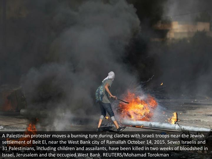 A Palestinian protester moves a burning tyre during clashes with Israeli troops near the Jewish sett...