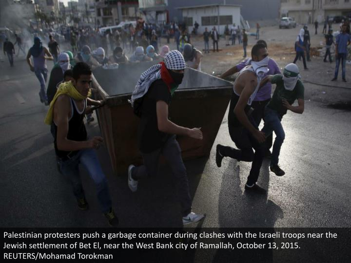 Palestinian protesters push a garbage container during clashes with the Israeli troops near the Jewish settlement of Bet El, near the West Bank city of Ramallah, October 13, 2015. REUTERS/Mohamad Torokman