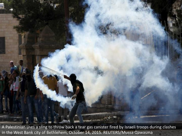 A Palestinian uses a sling to throw back a tear gas canister fired by Israeli troops during clashes in the West Bank city of Bethlehem, October 14, 2015. REUTERS/Mussa Qawasma