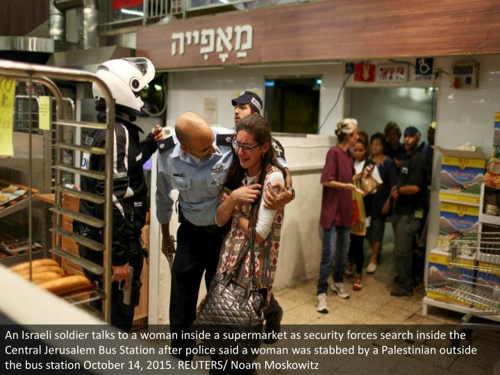 An Israeli soldier talks to a woman inside a supermarket as security forces search inside the Central Jerusalem Bus Station after police said a woman was stabbed by a Palestinian outside the bus station October 14, 2015. REUTERS/ Noam Moskowitz