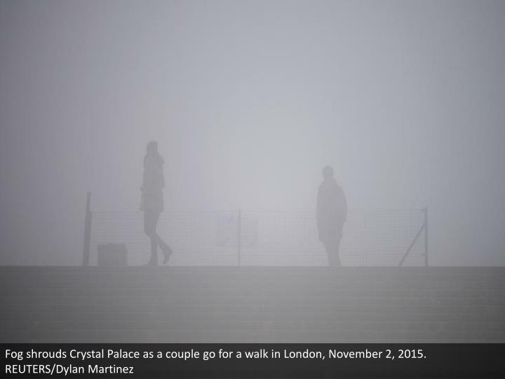Fog shrouds Crystal Palace as a couple go for a walk in London, November 2, 2015. REUTERS/Dylan Martinez