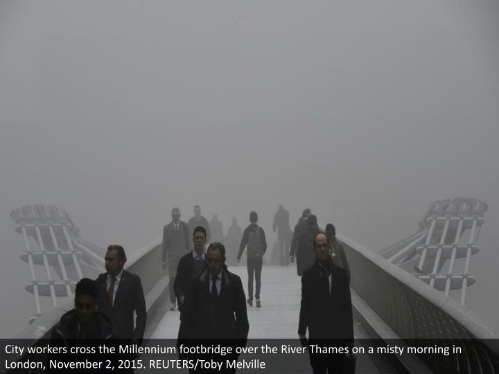 City workers cross the Millennium footbridge over the River Thames on a misty morning in London, November 2, 2015. REUTERS/Toby Melville