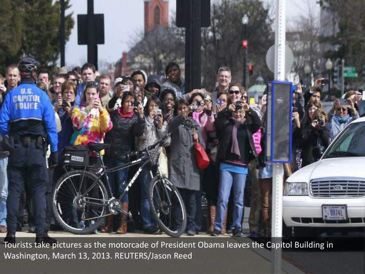 Tourists take pictures as the motorcade of President Obama leaves the Capitol Building in Washington, March 13, 2013. REUTERS/Jason Reed