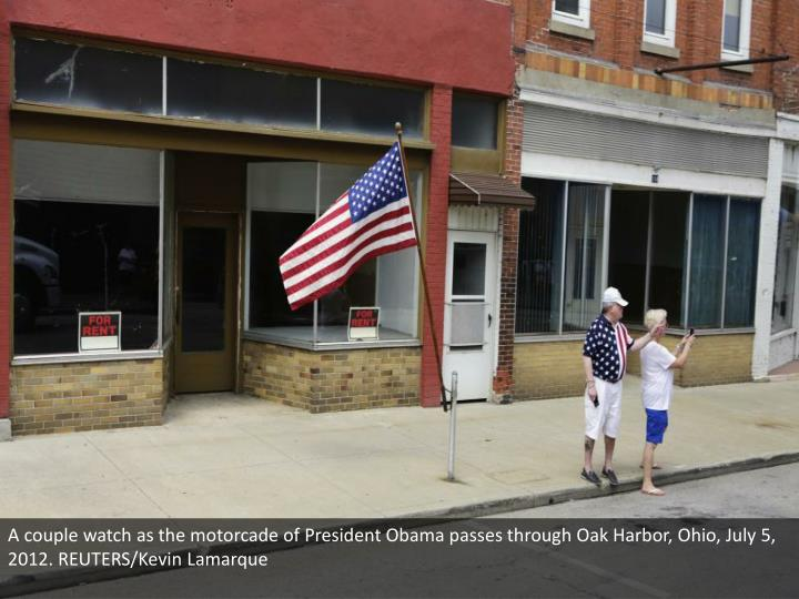 A couple watch as the motorcade of President Obama passes through Oak Harbor, Ohio, July 5, 2012. REUTERS/Kevin Lamarque