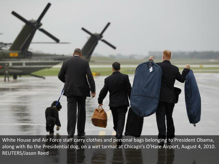 White House and Air Force staff carry clothes and personal bags belonging to President Obama, along with Bo the Presidential dog, on a wet tarmac at Chicago's O'Hare Airport, August 4, 2010. REUTERS/Jason Reed