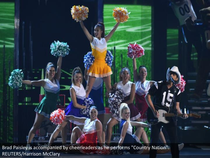 "Brad Paisley is accompanied by cheerleaders as he performs ""Country Nation"". REUTERS/Harrison McClar..."