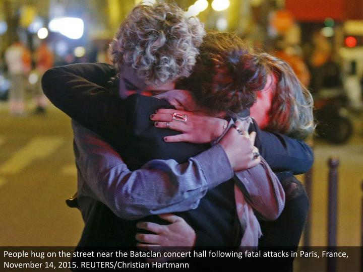People hug on the street near the Bataclan concert hall following fatal attacks in Paris, France, November 14, 2015. REUTERS/Christian Hartmann