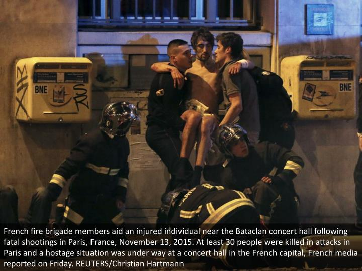 French fire brigade members aid an injured individual near the Bataclan concert hall following fatal...