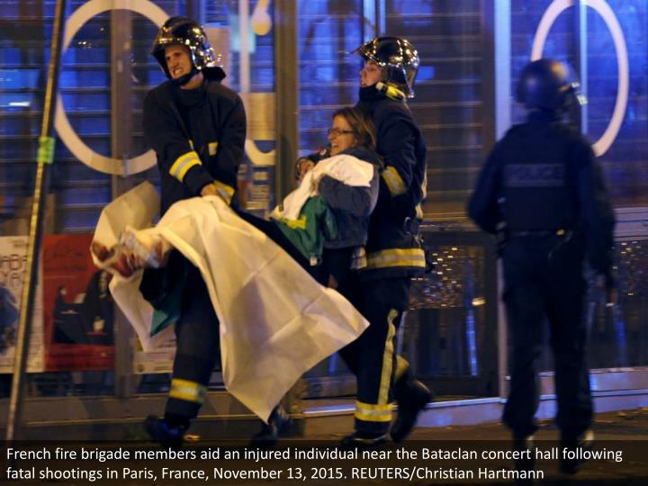 French fire brigade members aid an injured individual near the Bataclan concert hall following fatal shootings in Paris, France, November 13, 2015. REUTERS/Christian Hartmann