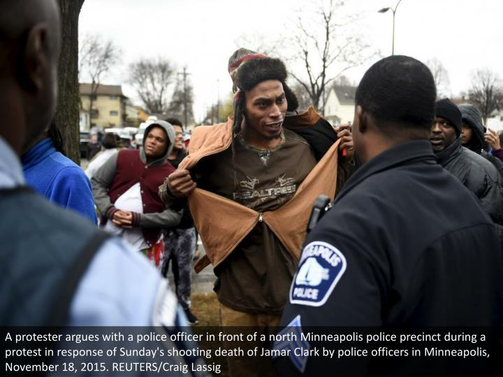 A protester argues with a police officer in front of a north Minneapolis police precinct during a protest in response of Sunday's shooting death of Jamar Clark by police officers in Minneapolis, November 18, 2015. REUTERS/Craig Lassig