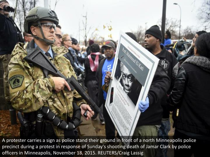 A protester carries a sign as police stand their ground in front of a north Minneapolis police preci...