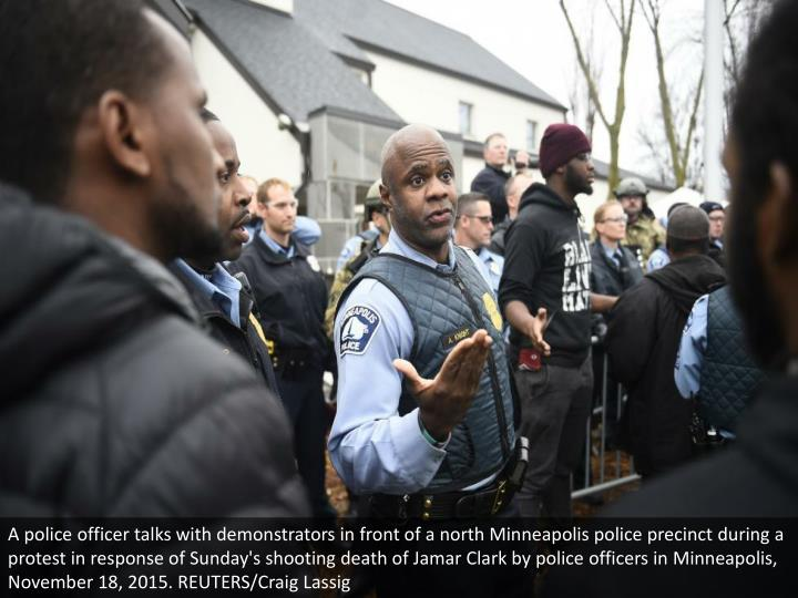 A police officer talks with demonstrators in front of a north Minneapolis police precinct during a protest in response of Sunday's shooting death of Jamar Clark by police officers in Minneapolis, November 18, 2015. REUTERS/Craig Lassig