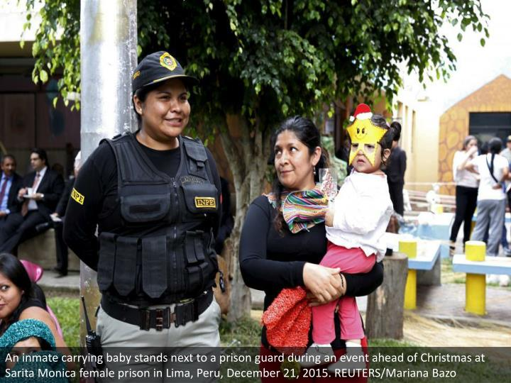 An inmate carrying baby stands next to a prison guard during an event ahead of Christmas at Sarita M...