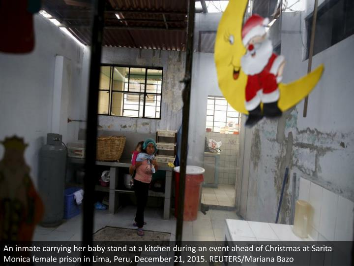 An inmate carrying her baby stand at a kitchen during an event ahead of Christmas at Sarita Monica female prison in Lima, Peru, December 21, 2015. REUTERS/Mariana Bazo