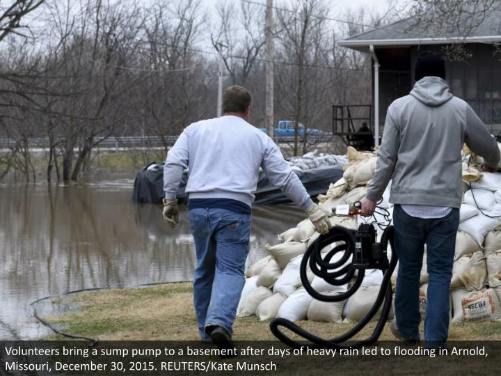 Volunteers bring a sump pump to a basement after days of heavy rain led to flooding in Arnold, Missouri, December 30, 2015. REUTERS/Kate Munsch