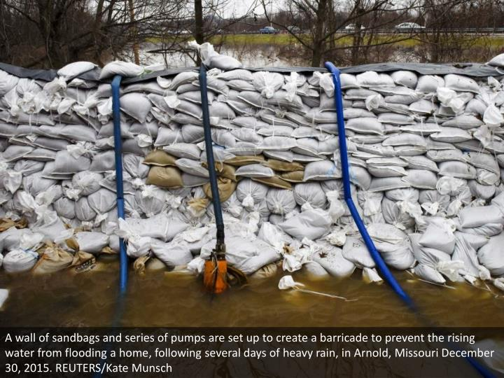 A wall of sandbags and series of pumps are set up to create a barricade to prevent the rising water from flooding a home, following several days of heavy rain, in Arnold, Missouri December 30, 2015. REUTERS/Kate Munsch
