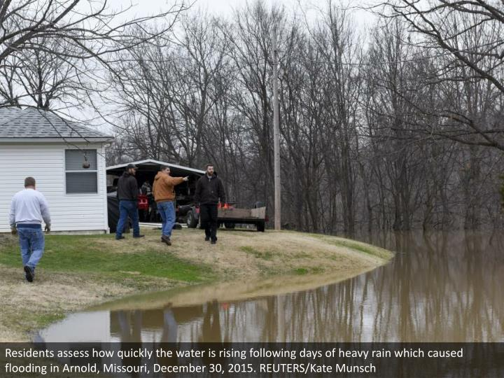 Residents assess how quickly the water is rising following days of heavy rain which caused flooding in Arnold, Missouri, December 30, 2015. REUTERS/Kate Munsch