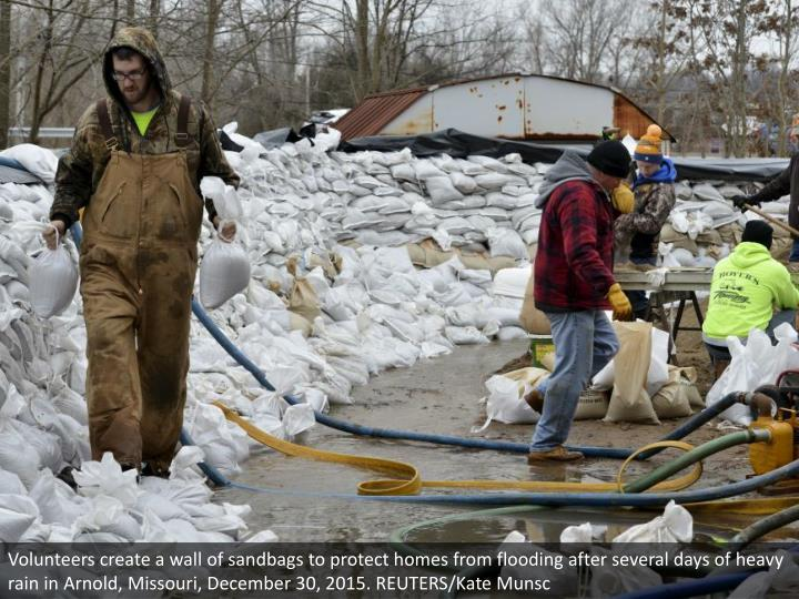 Volunteers create a wall of sandbags to protect homes from flooding after several days of heavy rain in Arnold, Missouri, December 30, 2015. REUTERS/Kate Munsc
