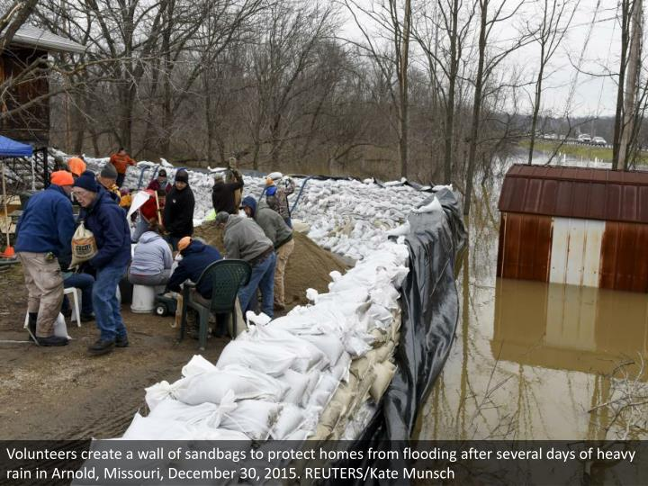 Volunteers create a wall of sandbags to protect homes from flooding after several days of heavy rain in Arnold, Missouri, December 30, 2015. REUTERS/Kate Munsch