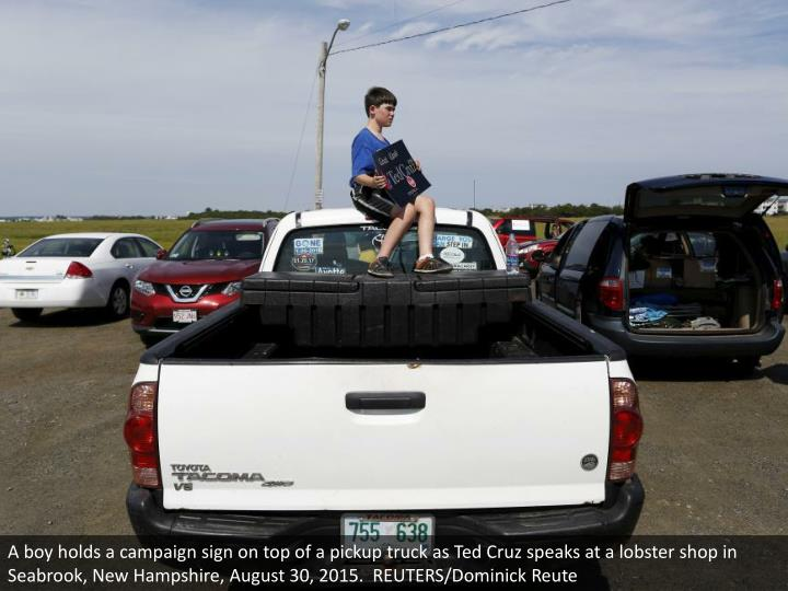 A boy holds a campaign sign on top of a pickup truck as Ted Cruz speaks at a lobster shop in Seabrook, New Hampshire, August 30, 2015.  REUTERS/Dominick Reute
