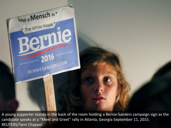 "A young supporter stands in the back of the room holding a Bernie Sanders campaign sign as the candidate speaks at a ""Meet and Greet"" rally in Atlanta, Georgia September 11, 2015.  REUTERS/Tami Chappel"