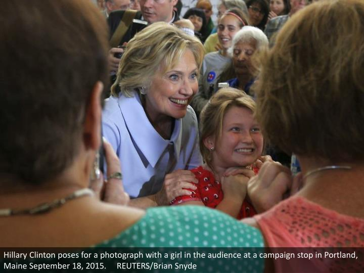 Hillary Clinton poses for a photograph with a girl in the audience at a campaign stop in Portland, Maine September 18, 2015.     REUTERS/Brian Snyde