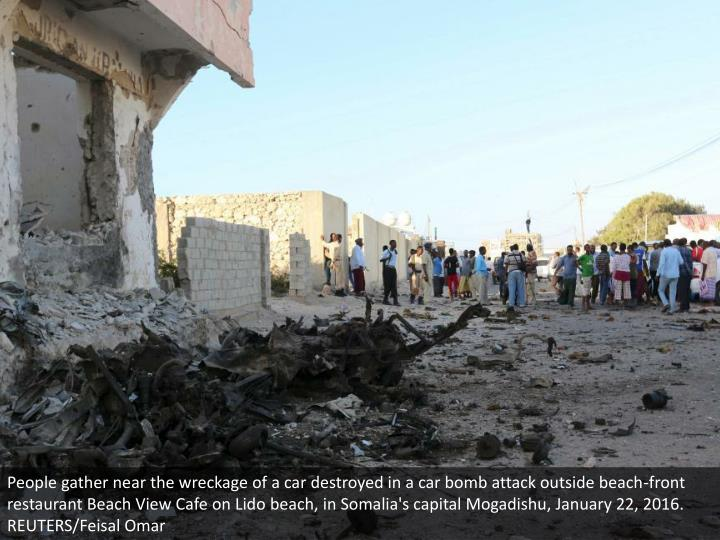 People gather near the wreckage of a car destroyed in a car bomb attack outside beach-front restaurant Beach View Cafe on Lido beach, in Somalia's capital Mogadishu, January 22, 2016. REUTERS/Feisal Omar