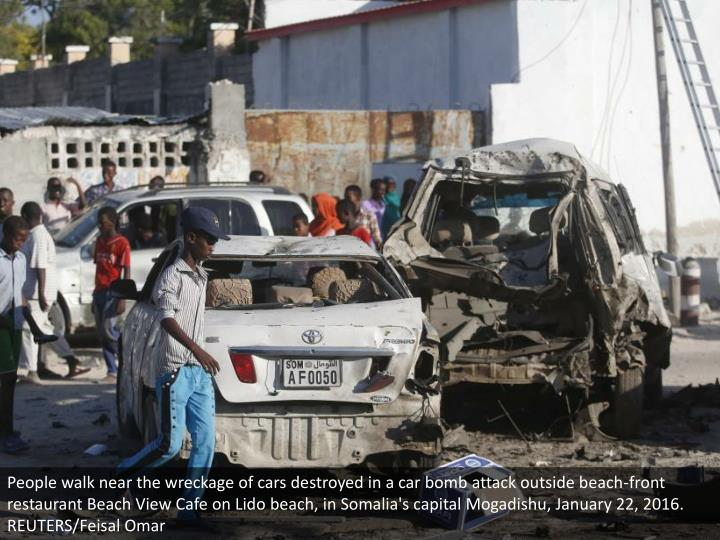 People walk near the wreckage of cars destroyed in a car bomb attack outside beach-front restaurant Beach View Cafe on Lido beach, in Somalia's capital Mogadishu, January 22, 2016. REUTERS/Feisal Omar