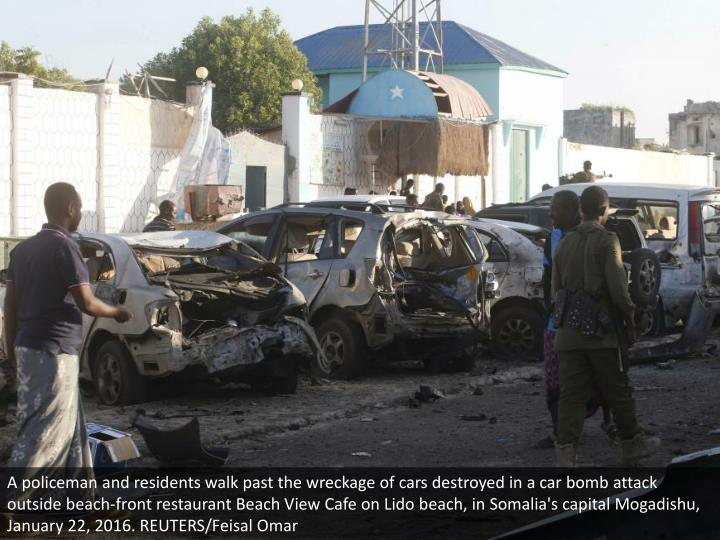 A policeman and residents walk past the wreckage of cars destroyed in a car bomb attack outside beach-front restaurant Beach View Cafe on Lido beach, in Somalia's capital Mogadishu, January 22, 2016. REUTERS/Feisal Omar