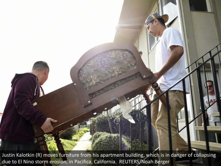 Justin Kalotkin (R) moves furniture from his apartment building, which is in danger of collapsing due to El Nino storm erosion, in Pacifica, California.  REUTERS/Noah Berger