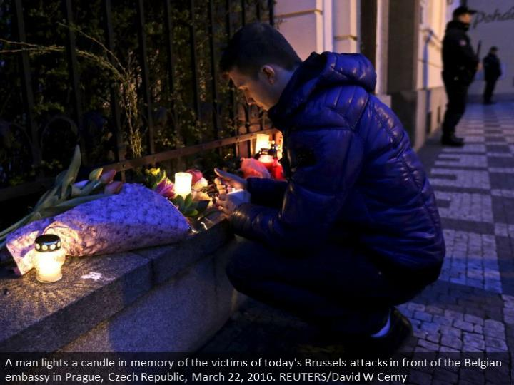A man lights a candle in memory of the victims of today's Brussels attacks in front of the Belgian embassy in Prague, Czech Republic, March 22, 2016. REUTERS/David W Cerny