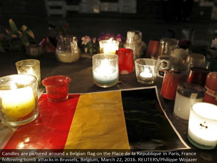Candles are pictured around a Belgian flag on the Place de la Republique in Paris, France following bomb attacks in Brussels, Belgium, March 22, 2016. REUTERS/Philippe Wojazer