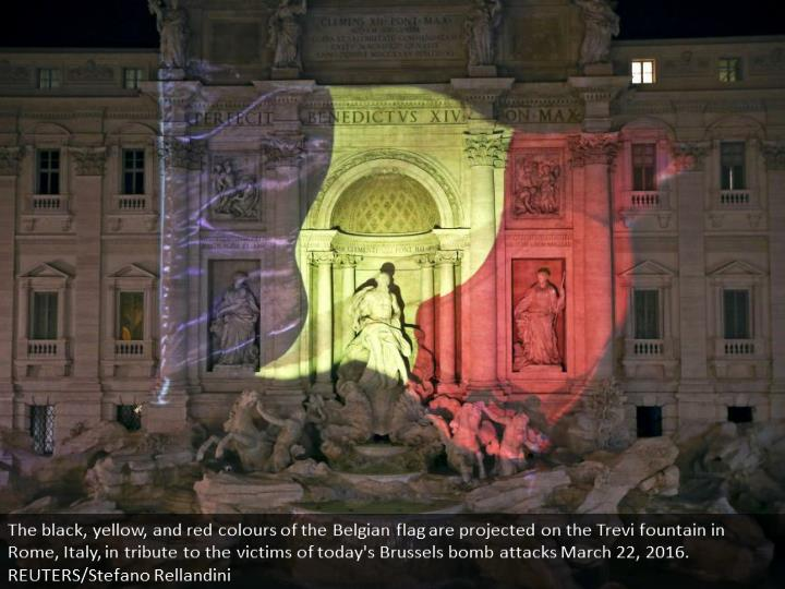 The black, yellow, and red colours of the Belgian flag are projected on the Trevi fountain in Rome, ...