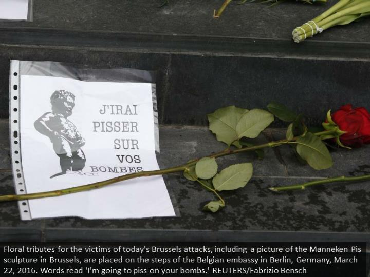 Floral tributes for the victims of today's Brussels attacks, including a picture of the Manneken Pis sculpture in Brussels, are placed on the steps of the Belgian embassy in Berlin, Germany, March 22, 2016. Words read 'I'm going to piss on your bombs.' REUTERS/Fabrizio Bensch