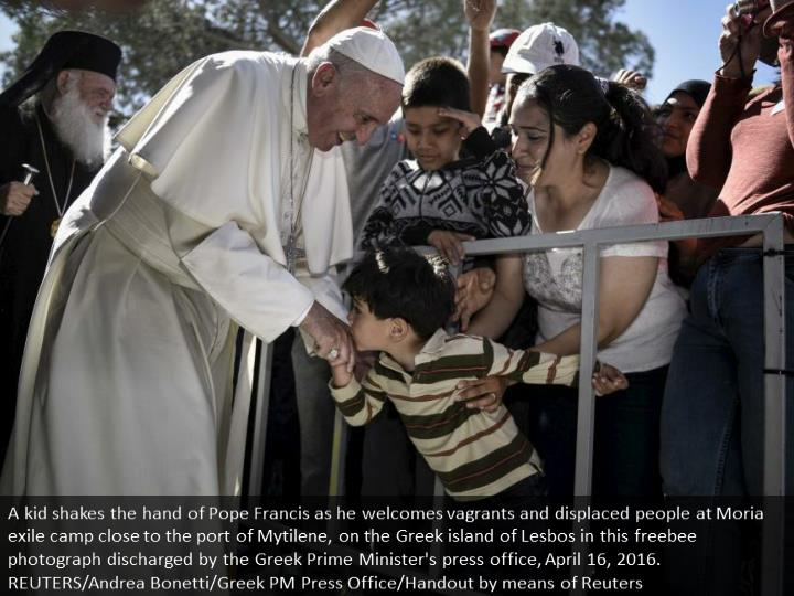 A boy shakes the hand of Pope Francis as he greets migrants and refugees at Moria refugee camp near ...