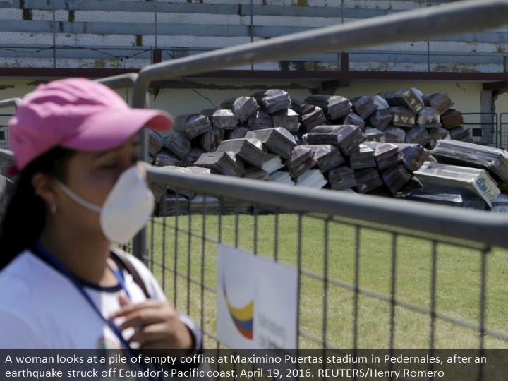 A woman looks at a pile of empty coffins at Maximino Puertas stadium in Pedernales, after an earthquake struck off Ecuador's Pacific coast, April 19, 2016. REUTERS/Henry Romero