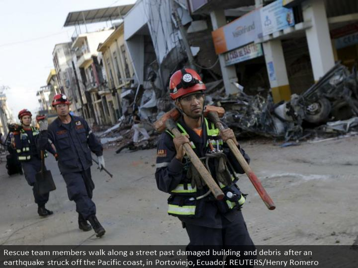 Rescue team members walk along a street past damaged building and debris after an earthquake struck off the Pacific coast, in Portoviejo, Ecuador. REUTERS/Henry Romero
