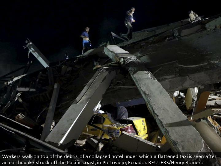Workers walk on top of the debris of a collapsed hotel under which a flattened taxi is seen after an earthquake struck off the Pacific coast, in Portoviejo, Ecuador. REUTERS/Henry Romero