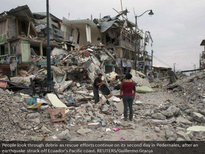 People look through debris as rescue efforts continue on its second day in Pedernales, after an earthquake struck off Ecuador's Pacific coast. REUTERS/Guillermo Granja